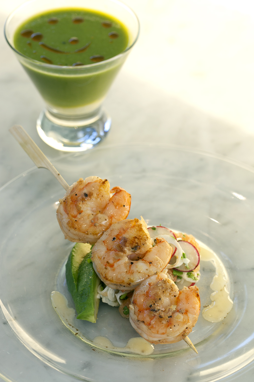 Purée of asparagus soup with goat cheese flan and harissa oil served with grilled wild shrimp with hearts of palm, avocado and grapefruit