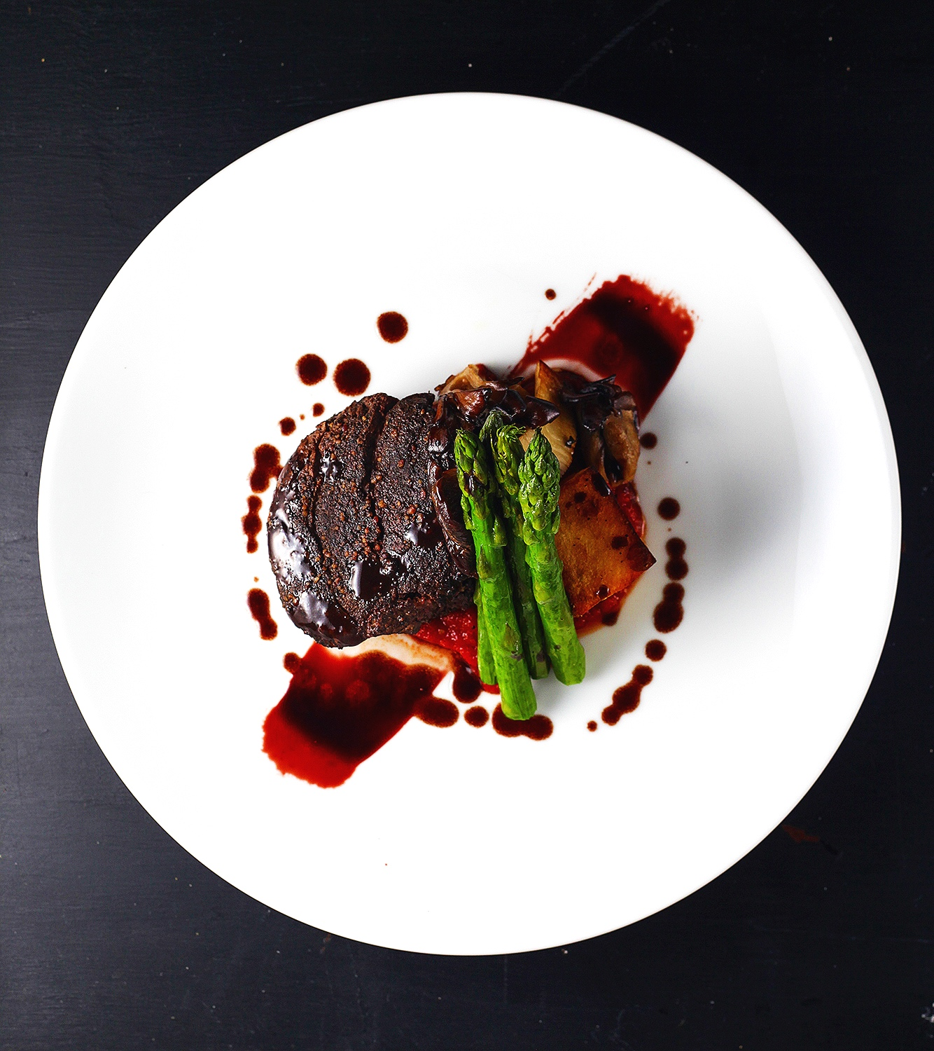 Beef tenderloin over polenta with red wine reduction and topped with asparagus