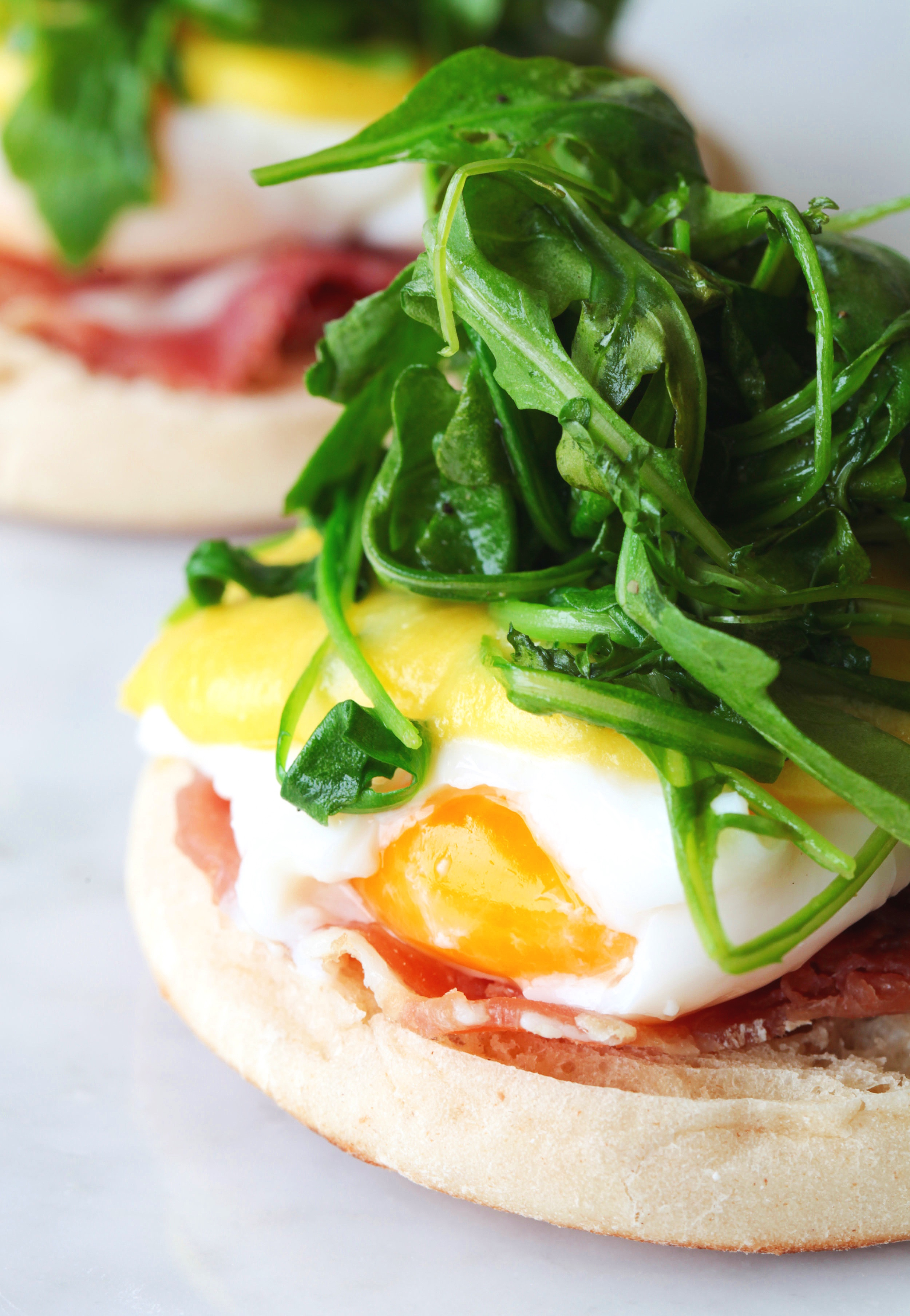 Breakfast sandwich with prosciutto, arugula and sunny side up egg on English muffin