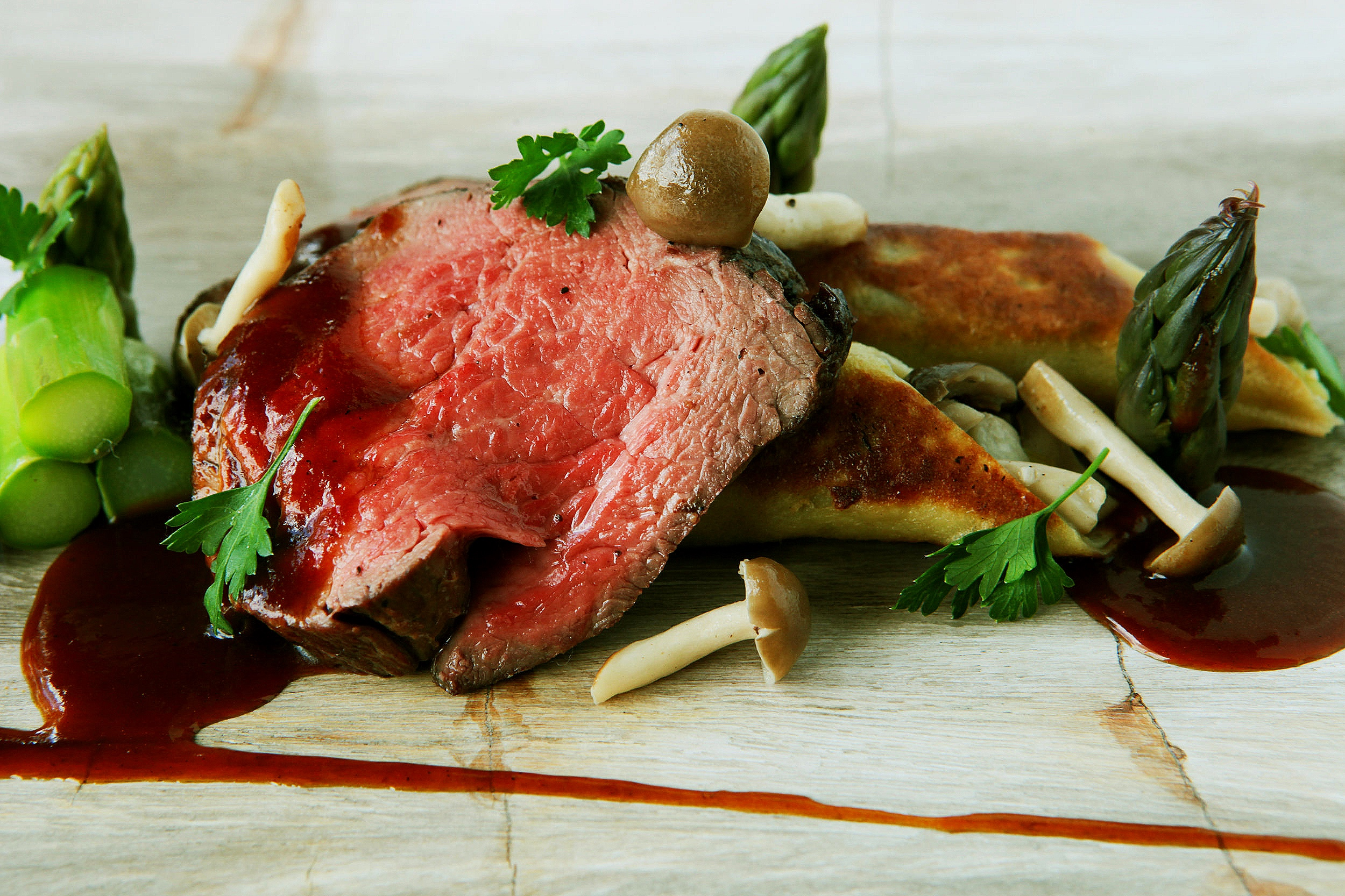 Beef tenderloin with red wine reduction, asparagus and chanterelle mushroom crepes