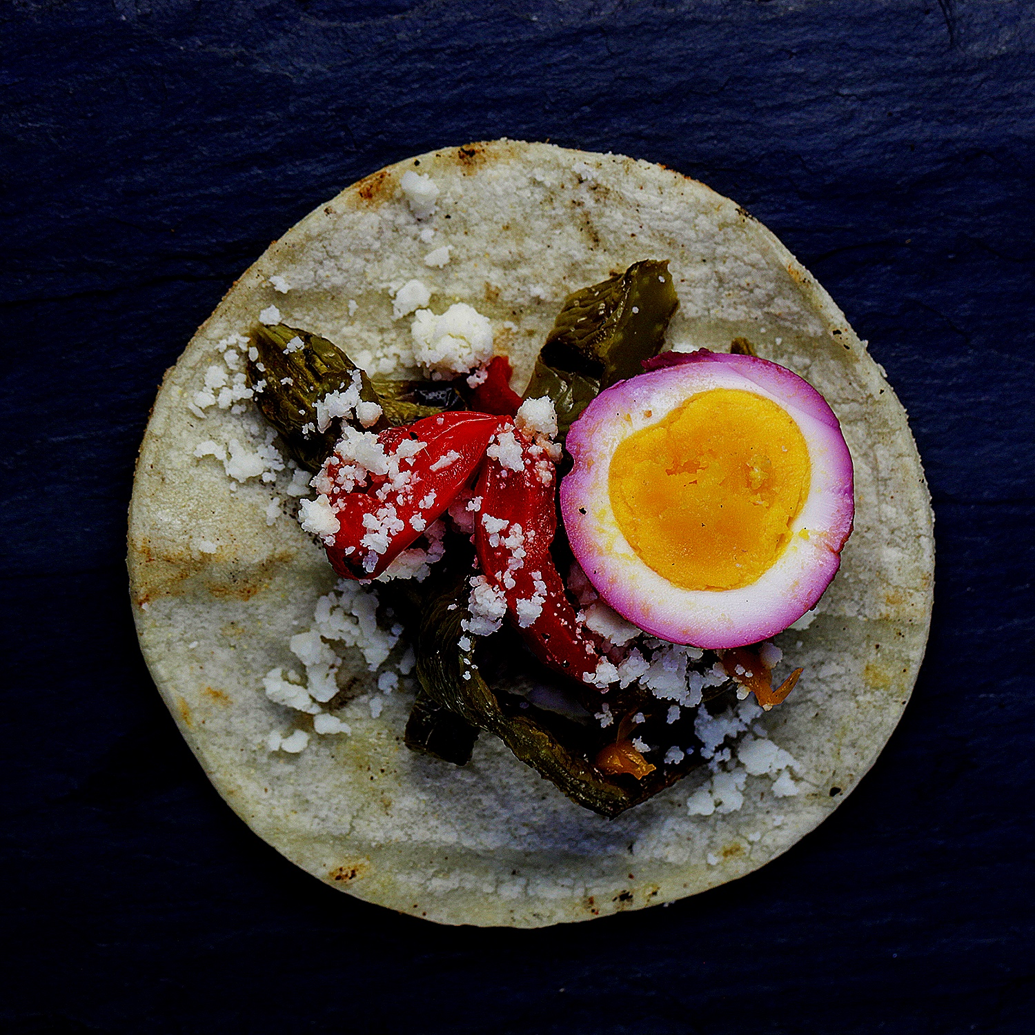 Vegetable taco with roasted asparagus and red pepper, medium boiled beet egg and cojita