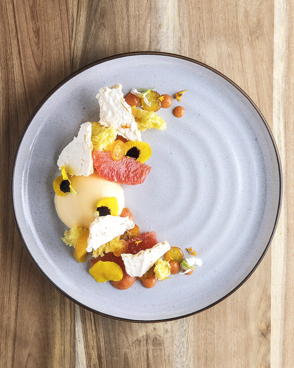 Orange panna cotta, orange sponge cake, meringue shards, candied kumquats, citrus segments, serrano oil