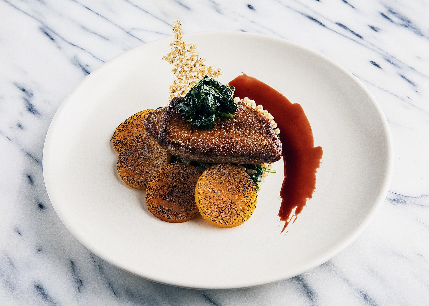 Smoked duck breast with barley chip, pickled pumpkin, spinach, and sherry reduction