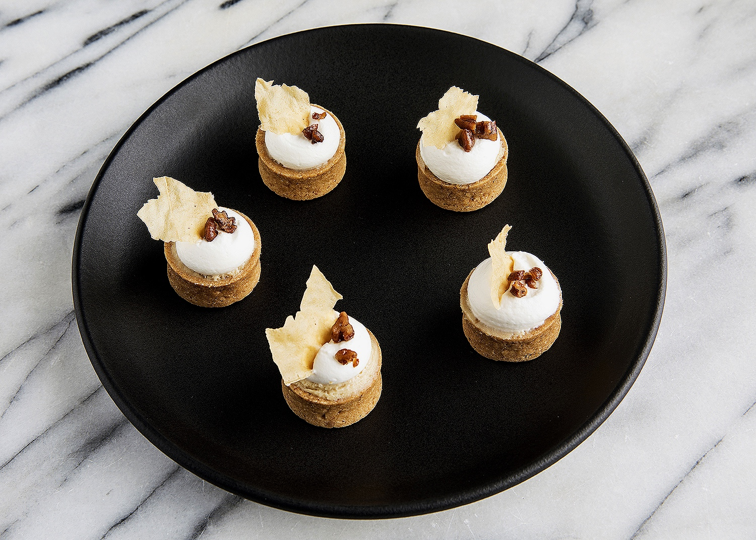Maple tartlets with whipped cream and walnut pieces
