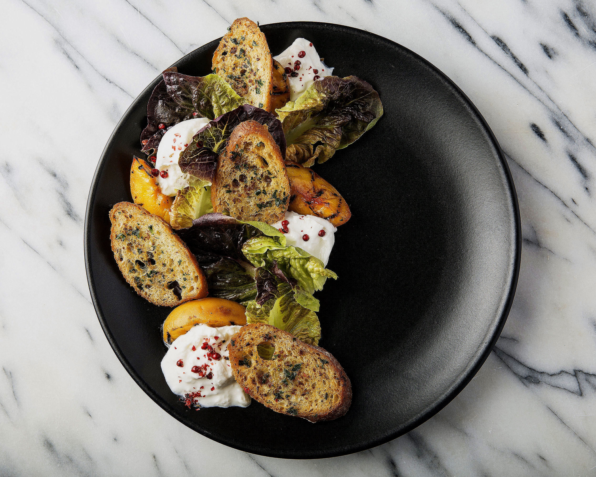 Red lettuce with grilled tree ripened peaches, burrata cheese, garlic herb crostini, crushed red pepper, and white balsamic vinaigrette