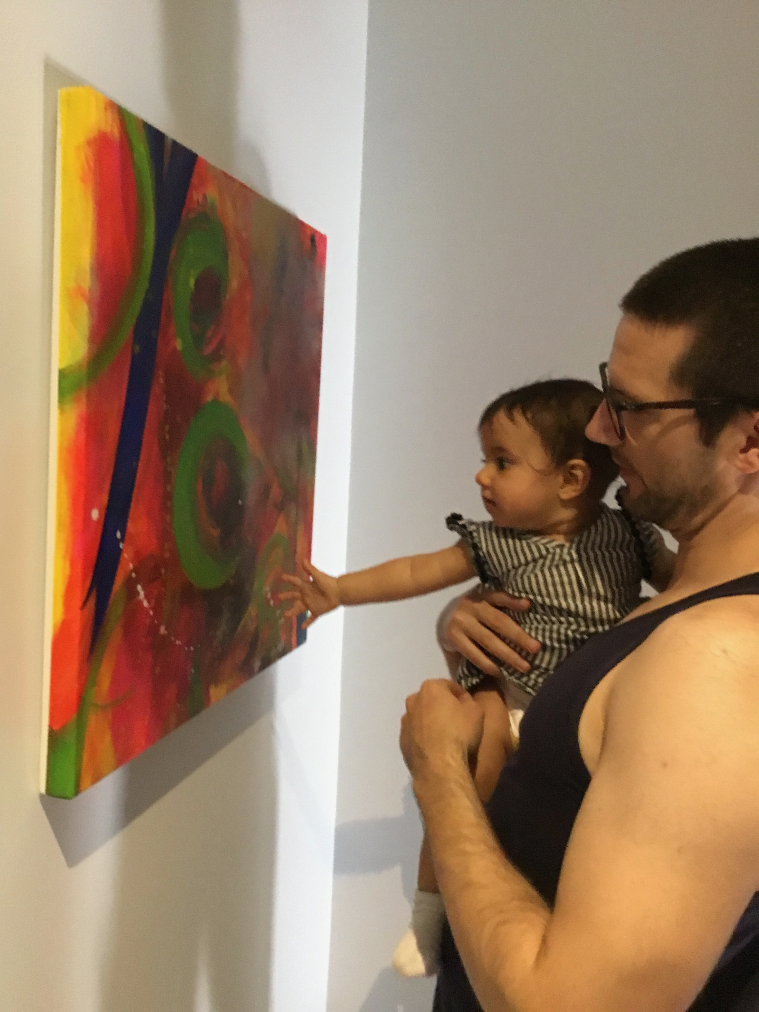 Naya, aged 9 months, with her father, looking at  Here they come,  acrylic on canvas, Lynne Cameron.
