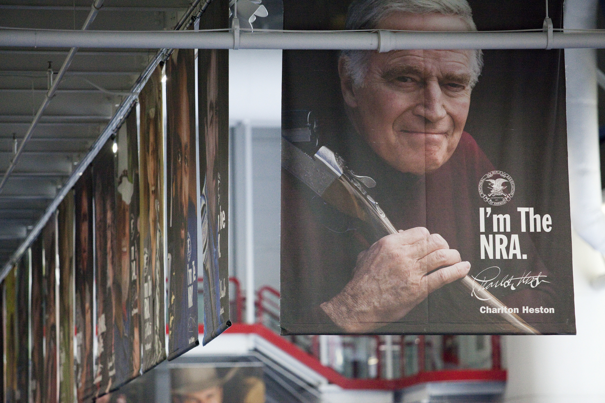 A poster of Charlton Heston, along with other celebrity members, hangs in the George R. Brown Center at the 2013 National Rifle Association Meeting and Exhibits May 2, 2013 in Houston.