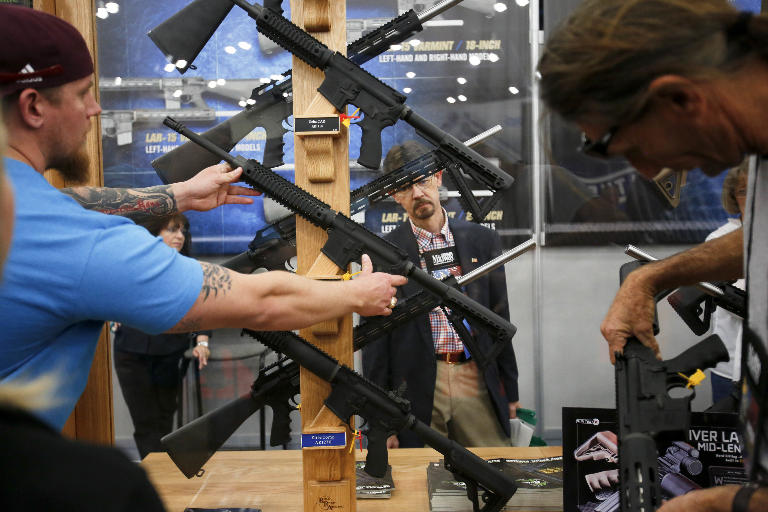 Attendees look at AR15 rifles at the 2013 National Rifle Association Meeting and Exhibits May 4, 2013 in Houston.