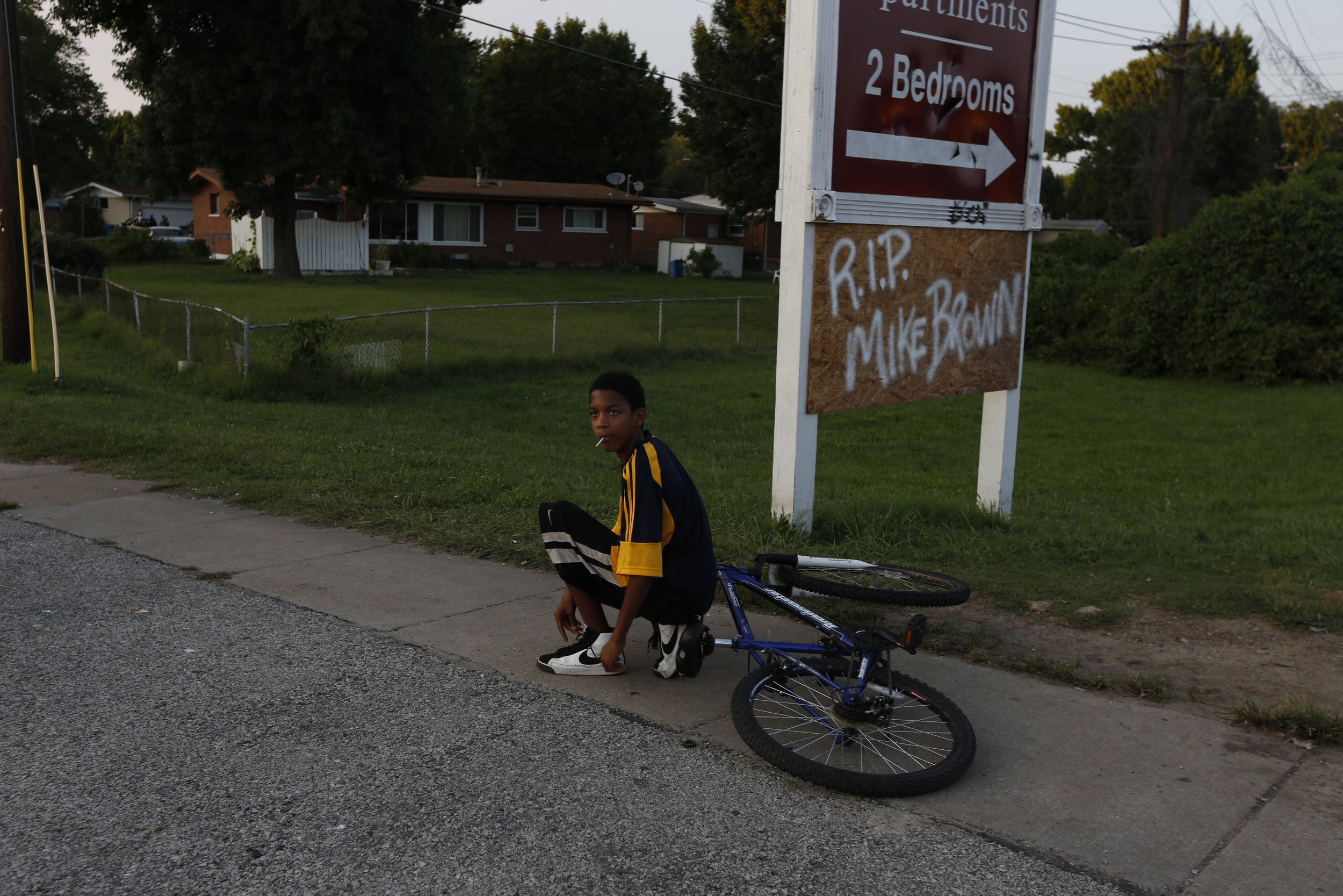 A child stops to tie his shoe along W. Florissant Ave. August 19, 2014 in Ferguson, MO. W. Florissant Ave. has been the location of protests and occasional rioting related to the shooting of an unarmed Michael Brown by Ferguson police.