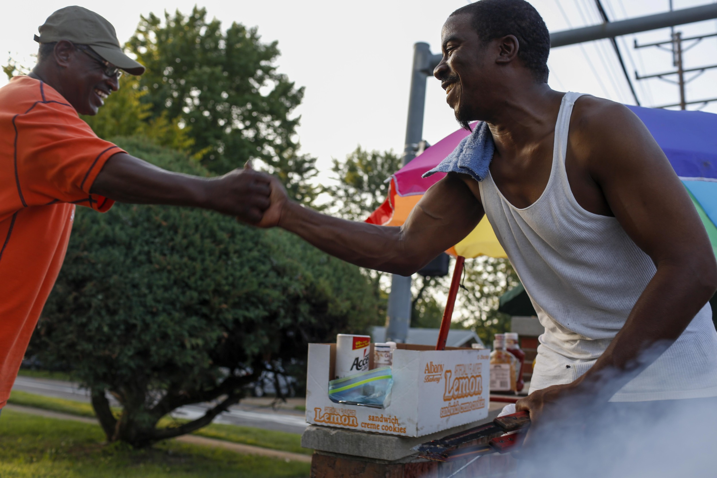 Greg Jones, left, greets Walter Nash as Nash cooks free BBQ on W. Florissant for protestors August 20, 2014 in Ferguson, MO less than a mile away from where Michael Brown was shot and killed by a Ferguson police officer.