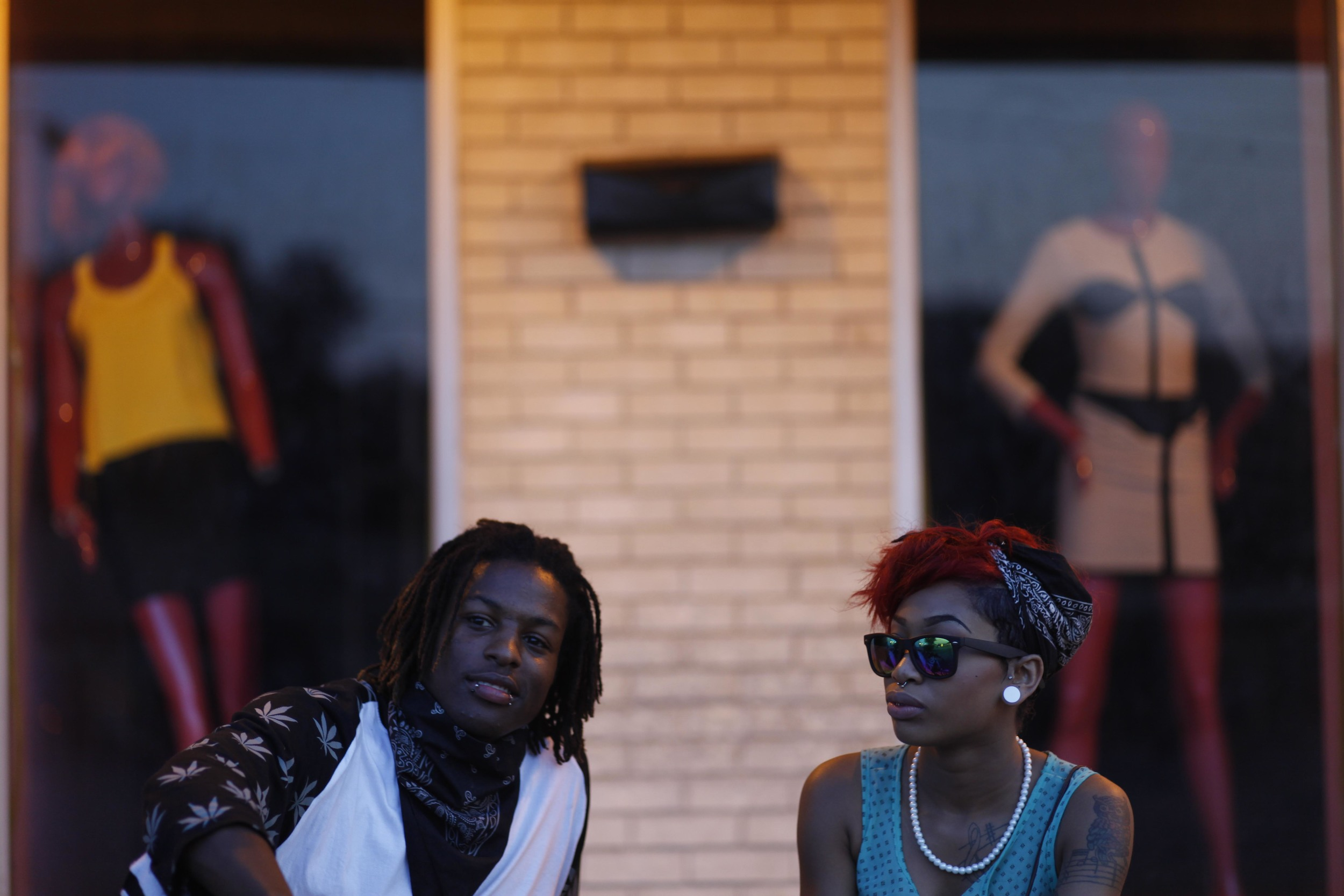 Asia Jackson, left, and Taylor Barnes, sit in front of a W. Florissant Ave. boutique August 20, 2014 in Ferguson, MO. Both are from Ferguson and were out to support the protest.