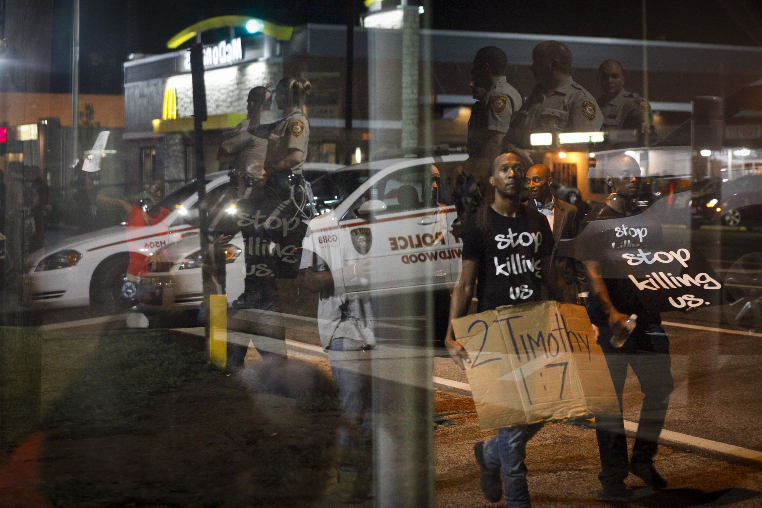 Protestors walk past a bus stop at W. Florissant and Ferguson Ave. as law enforcement officers are reflected in the bus stop window August 20, 2014 in Ferguson, MO.