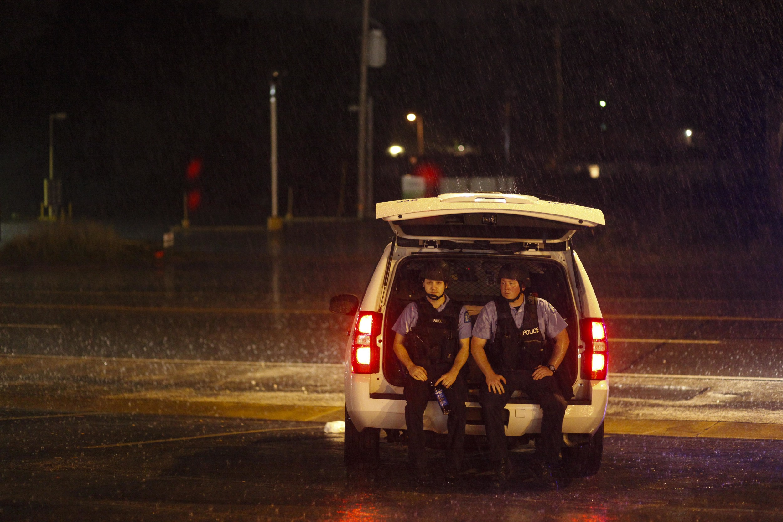 Two police officers wait out a passing thunderstorm along the protest route on W. Florissant Ave. August 20, 2014 in Ferguson, MO.
