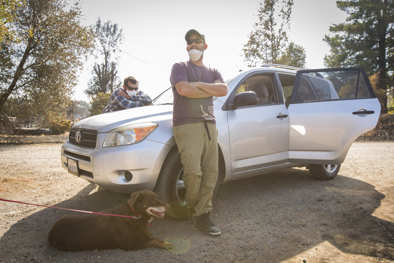 Eli Monroe, center, stands by his car he used to barely escape the Mendocino-area wildfire on his family's property Oct. 15, 2017 in Redwood Valley, CA.