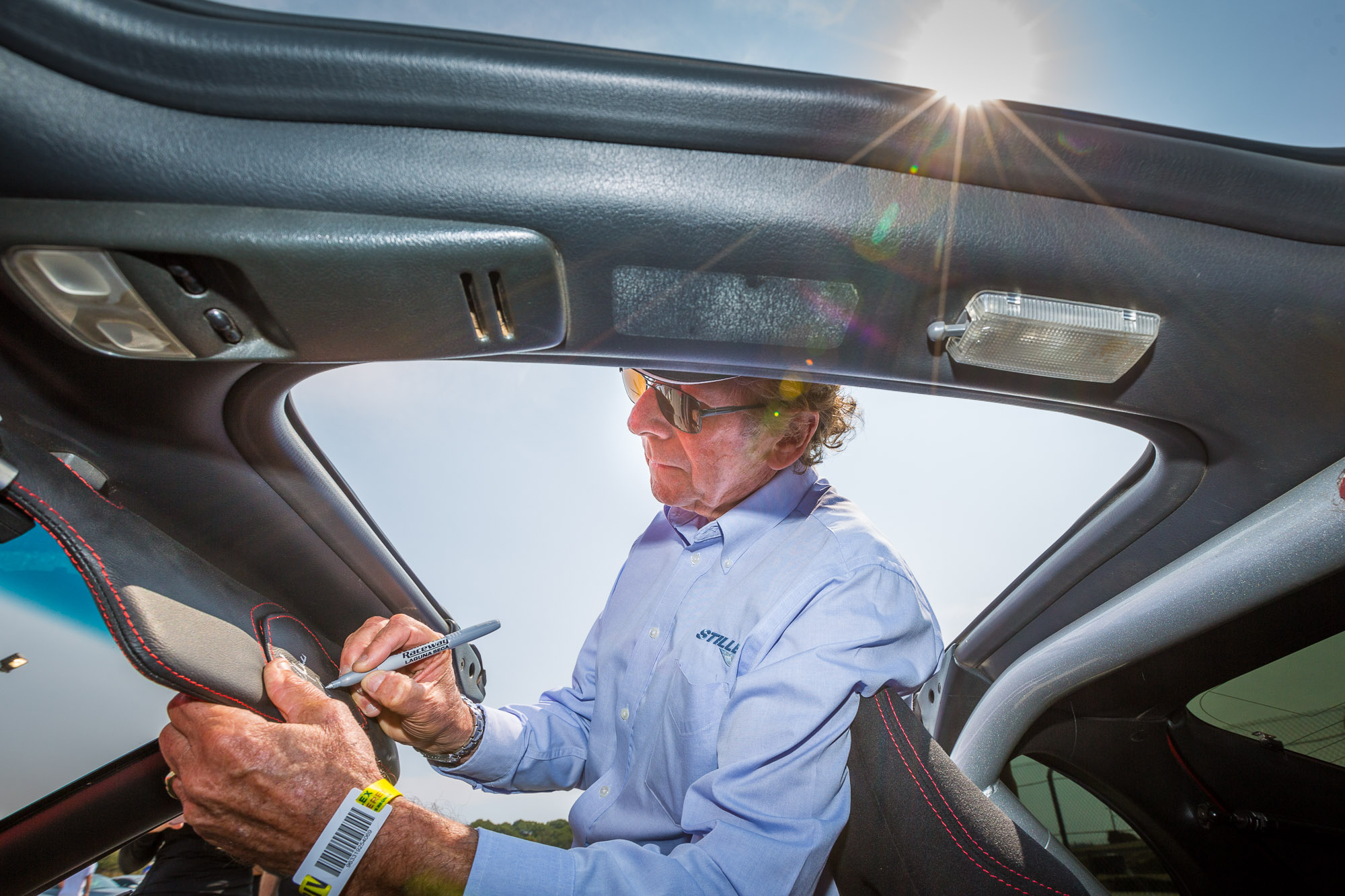 Nissan racing legend Steve Millen autographs a fan's vehicle at The Rolex Monterey Motorsports Reunion, where Nissan is the featured marque, on Saturday, Aug. 25, 2018, in Salinas, Calif. (Eric Kayne/AP Images for Nissan)