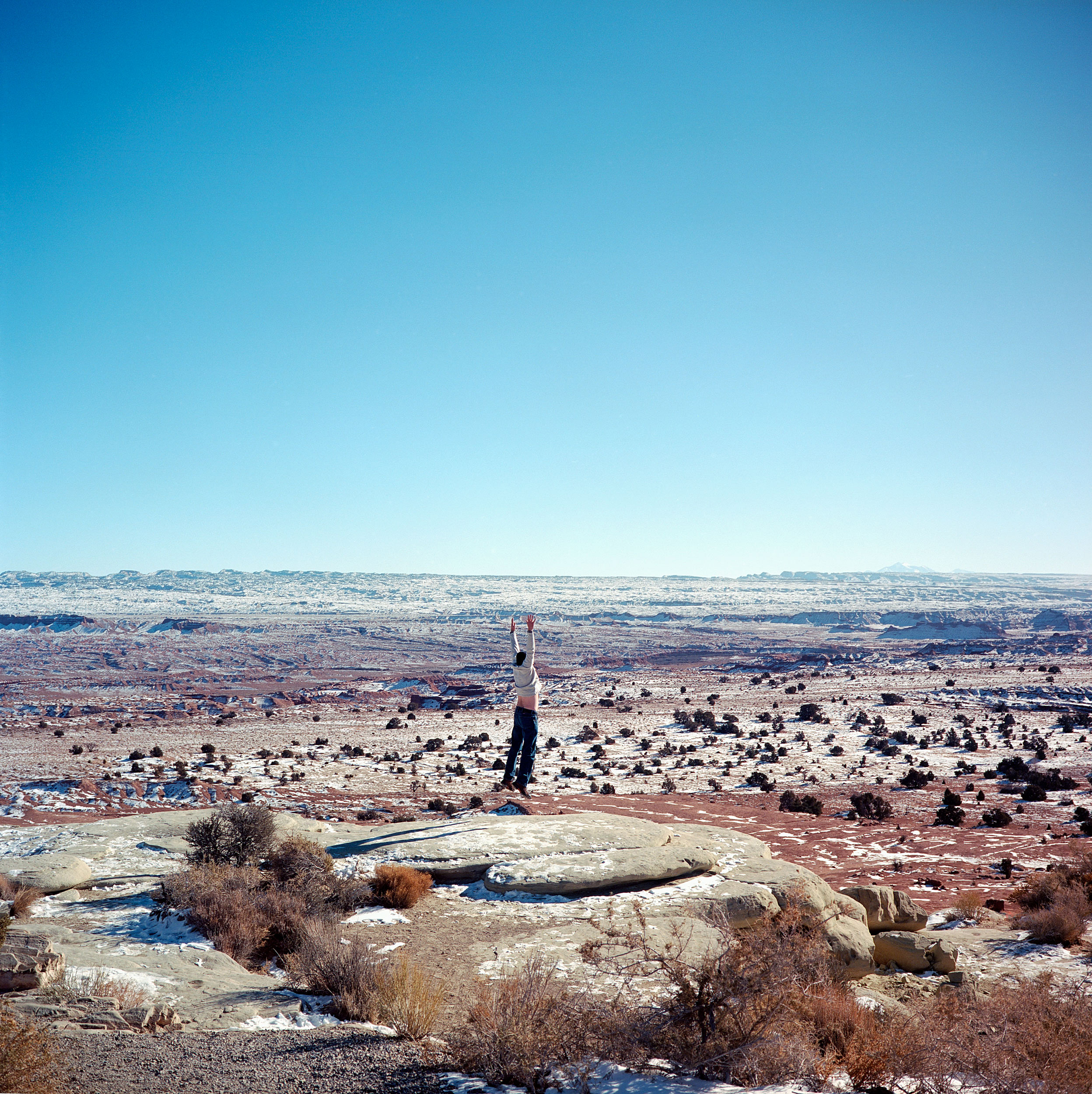 A man jumps in the air for a photograph at the Sand Bench Viewing Area in Utah. The pullout features spectacular views of the San Rafael Swell, an area managed by the Bureau of Land Management, consists of a giant dome-shaped anticline of sandstone, shale, and limestone that was pushed up during the Paleocene Laramide Orogeny 60-40 million years ago.