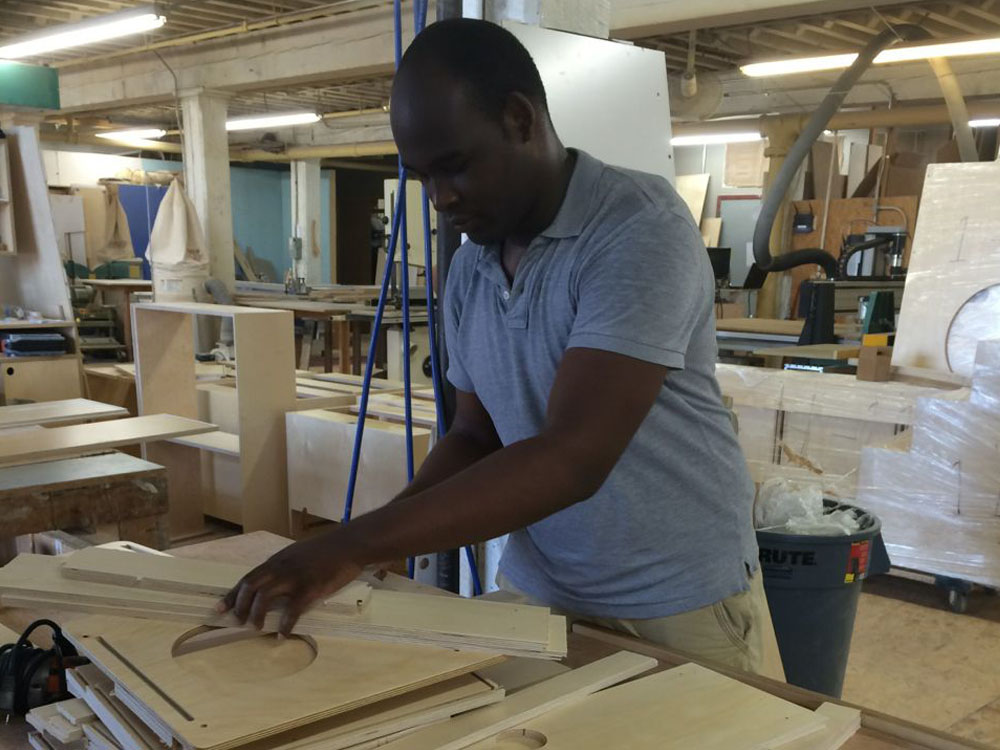 Tulio Santos organizing the CNC-cut wood parts for sanding and assembly
