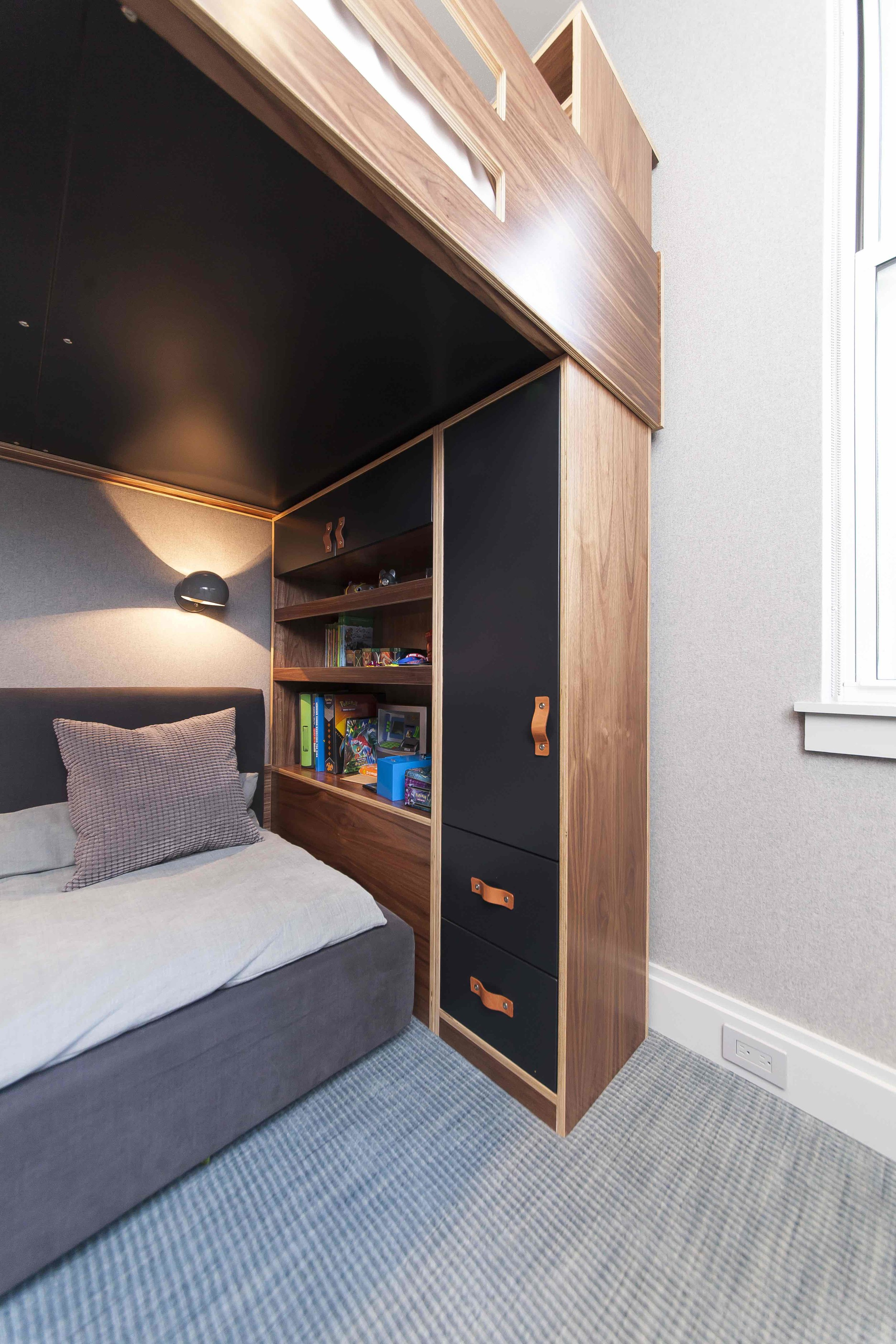 Custom cabinet holding up a loft bed.