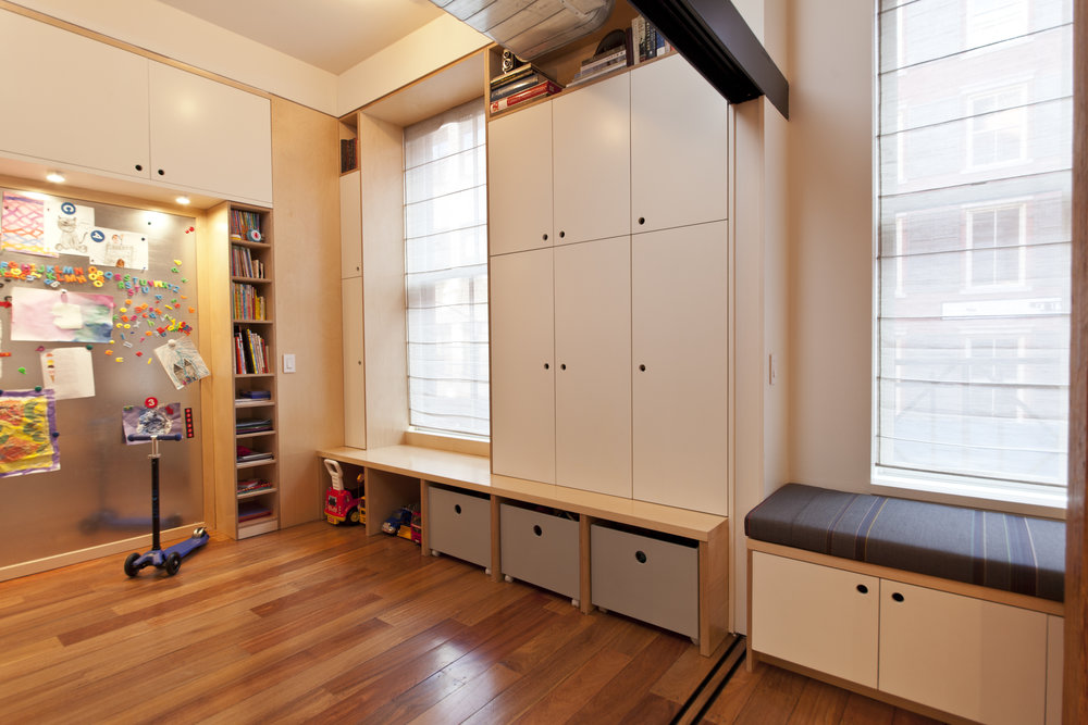 A built in playroom with under window storage benches.