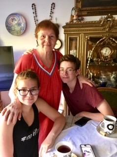 Mom, 83, drinking tea with grandchildren.