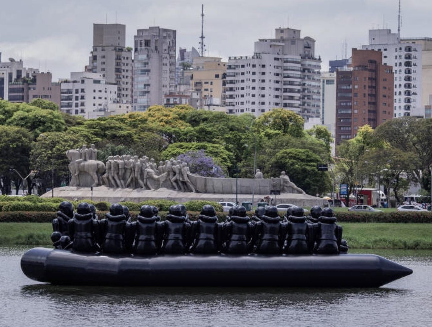 The Law of the Journey, um gigantesco bote inflável com imigrantes igualmente infláveis que flutuou por 24 horas no lago do Parque Ibirapuera antes da abertura da maior exibição individual do artista.