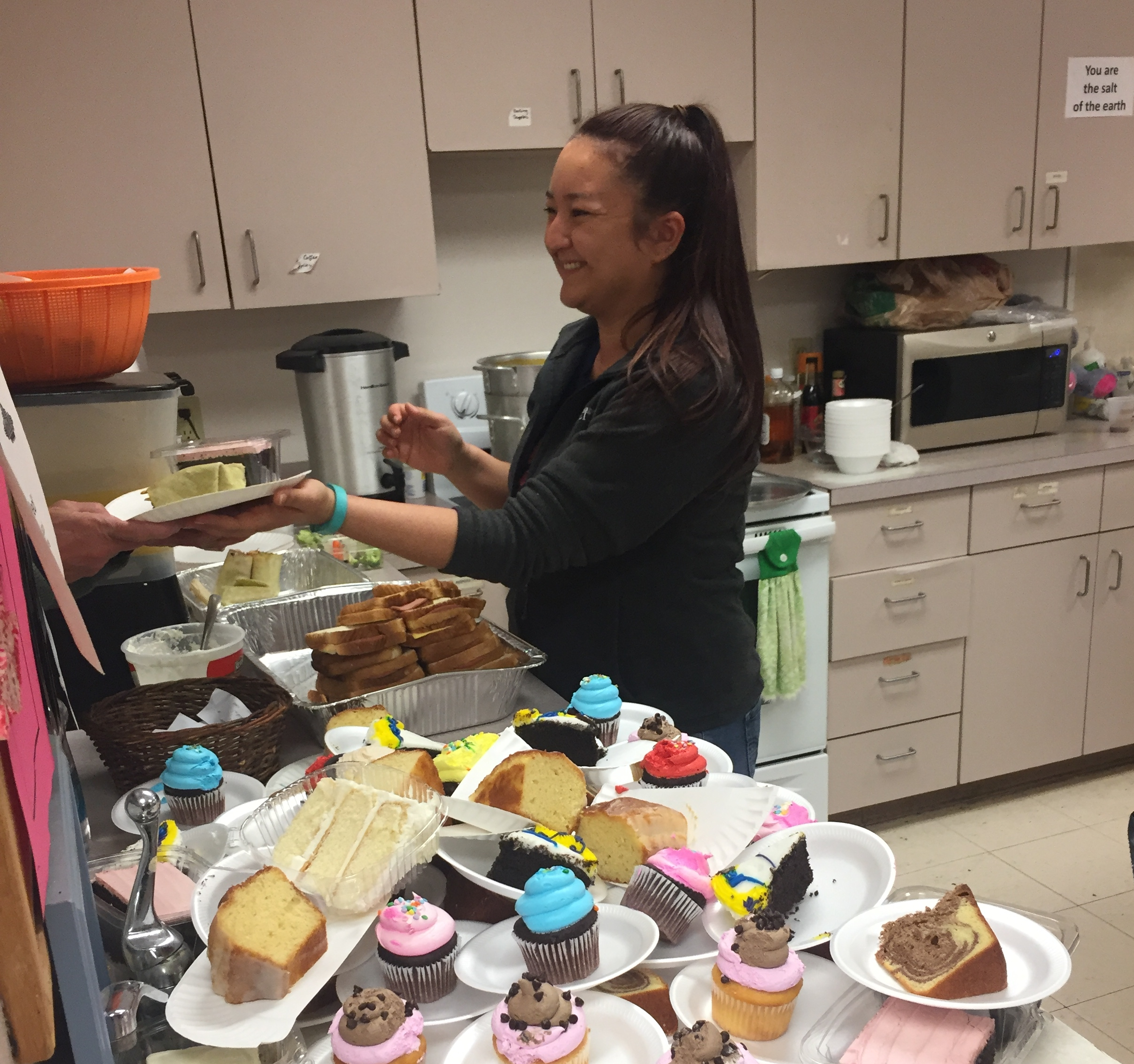 Crisis Ministry volunteer Jenny Brooks serves dessert to a client during a recent soup kitchen lunch.