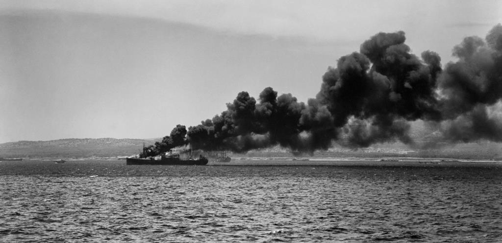 Operation Husky, invasion of Sicily, 10 July 1943: four miles south of Syracuse in 'Acid North' sector, an ammunition supply ship hit by enemy bombs burns close to the assault beaches. Landing craft can be seen on the shoreline below the smoke. (Lt F.G. Roper, R.N., Admiralty Official Collection, IWM A 18091).
