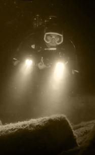My brother took this image of me diving at night on a wreck that inspired a scene in the novel.