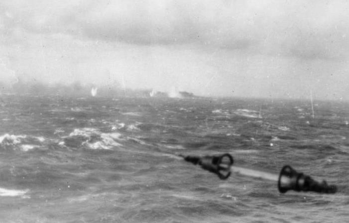 The last known photograph of Bismarck, shells falling around her and trailing smoke, taken from the railing of a British ship on 27 May 1941 (Lt J.H. Smith, RN, IWM A 4386).