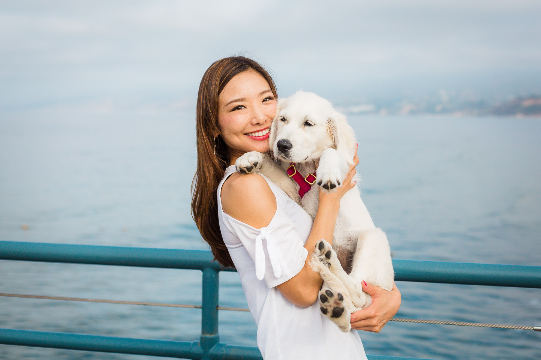 asian-girl-holding-cream-golder-retriever-puppy-beach.jpg