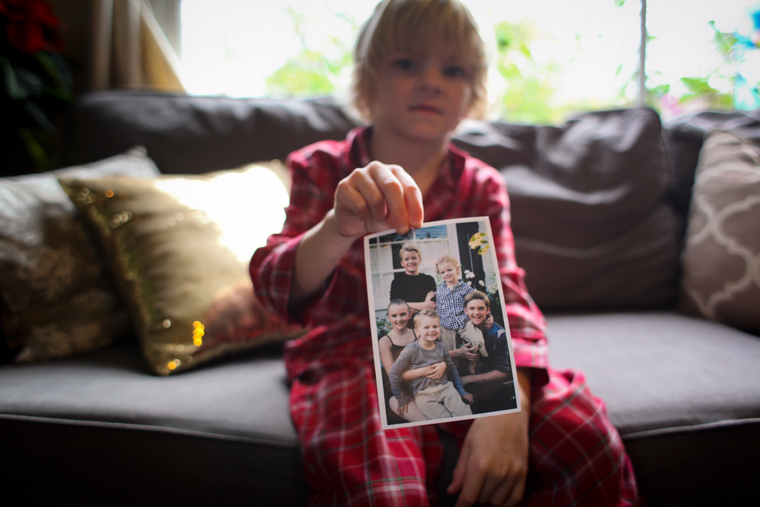 """Washington, """"Osh"""" age 6, shows me a photo of the kids from two years ago, before Teddy was born."""