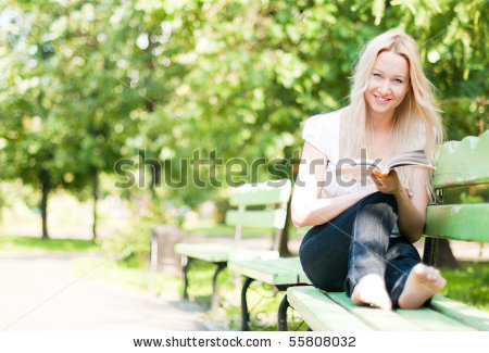 stock-photo-young-woman-sitting-on-bench-in-park-reading-book-smiling-and-looking-into-the-camera-55808032.jpg