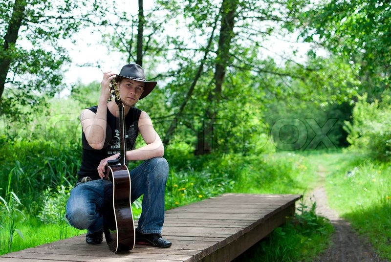 2860365-man-with-a-guitar-sits-on-the-bridge-in-the-woods.jpg