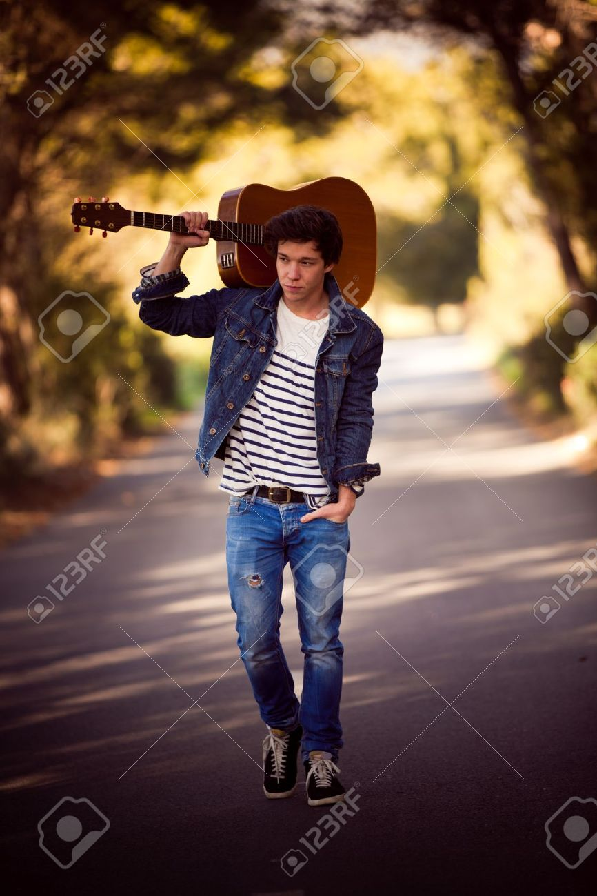 17888718-drifter-man-with-guitar-walking-outdoors-Stock-Photo-handsome.jpg