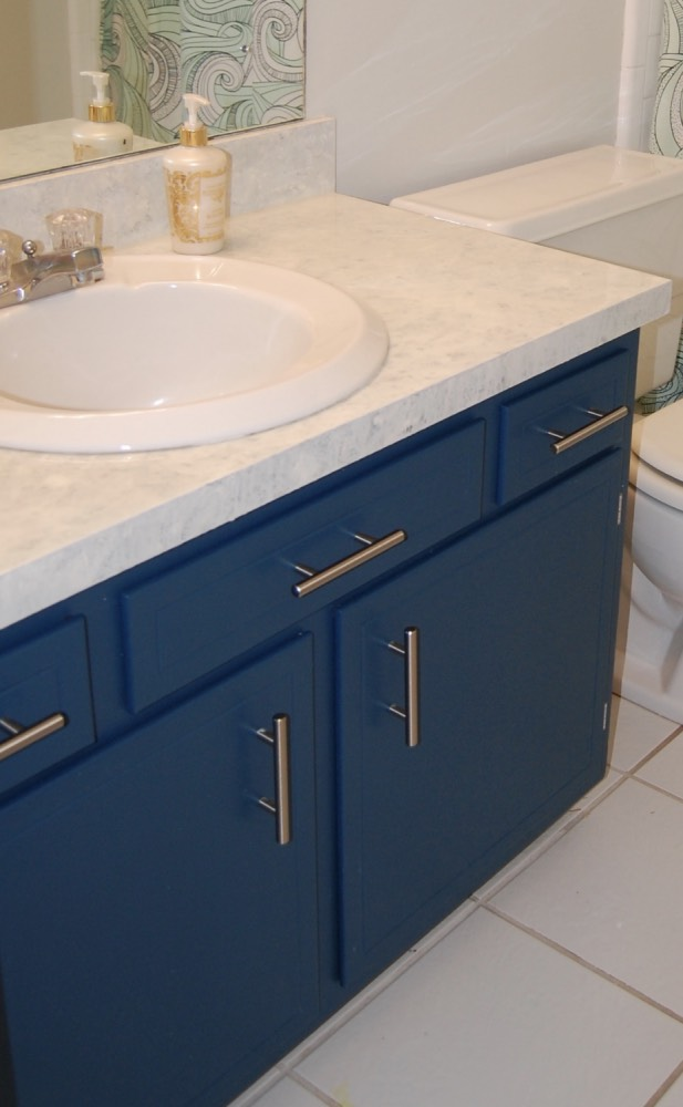 The bathroom cabinet after a coat of paint, new hardware, and a refinished countertop.