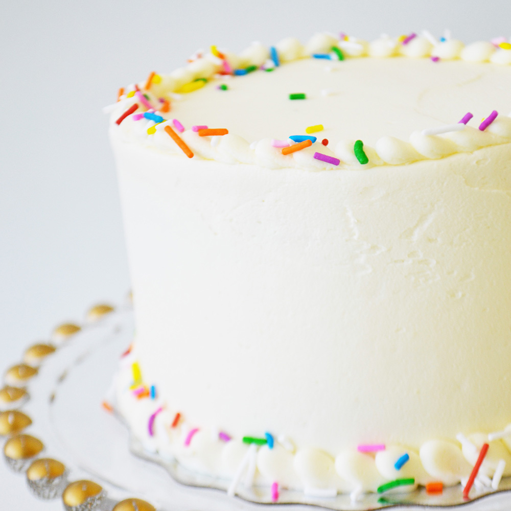 Vanilla Cake  - Traditional vanilla cake layered with vanilla buttercream, decorated with vermicelli sprinkles.
