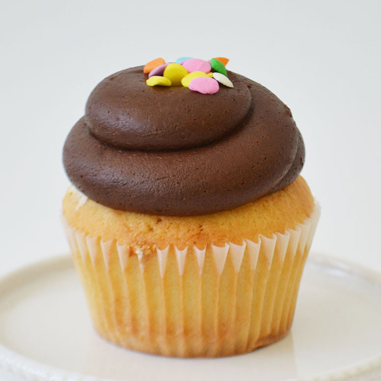 Vanilla Chocolate Cupcake -  Dense vanilla cake topped with rich chocolate buttercream and confetti sprinkles.