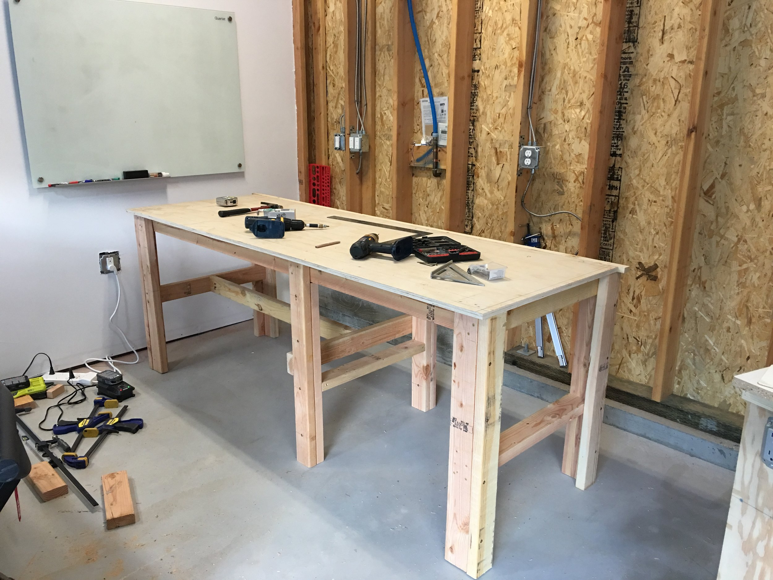 """Added a sheet of 3/4"""" plywood, squaring it up as I screw it down onto the legs and apron."""