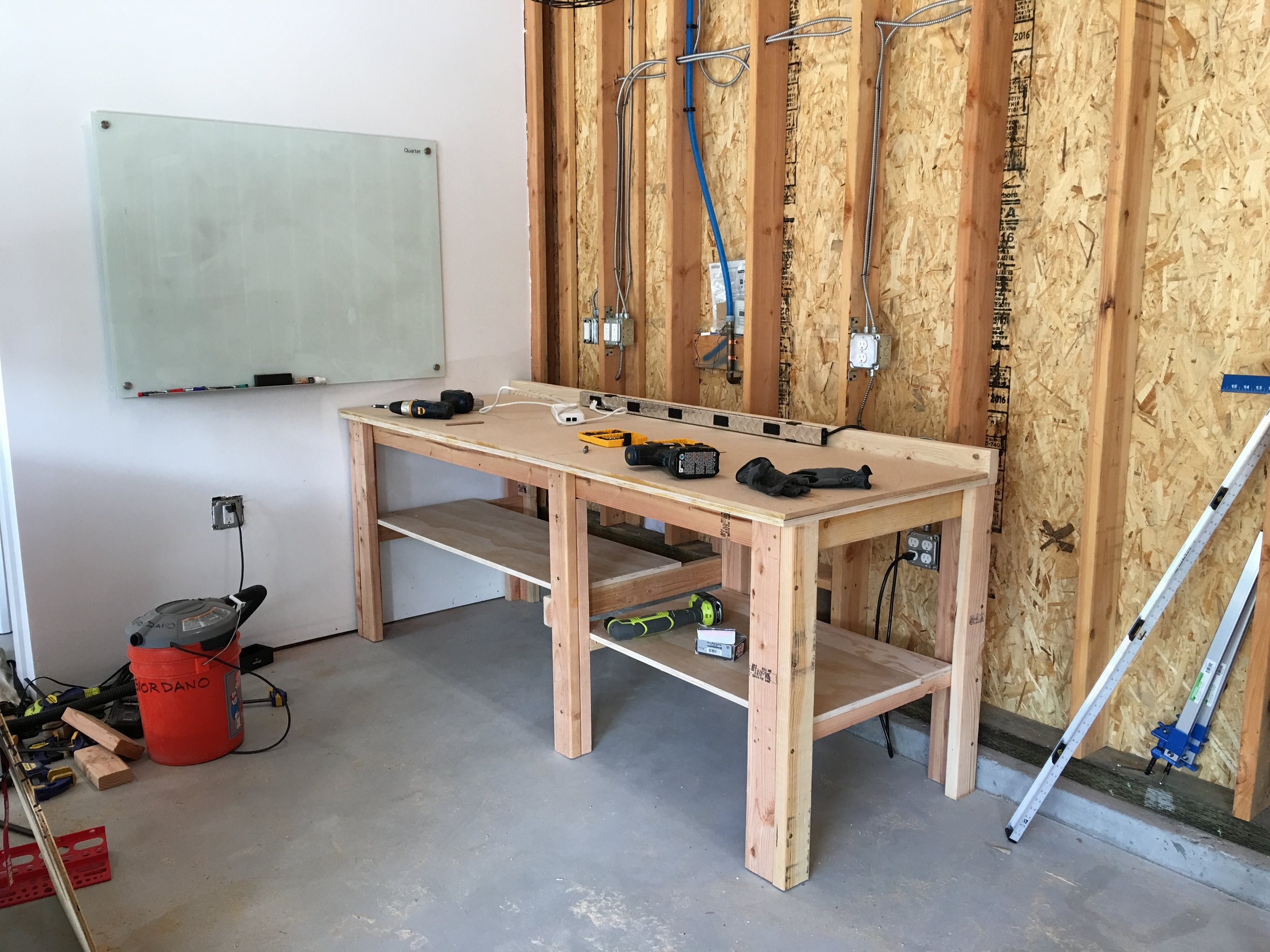 """Then added a 1/2"""" sheet of MDF. MDF is super smooth and the extra layer adds structure and density to the workbench.  Also added shelves underneath - plenty of room for the big Rubbermaid plastic bins.  Includes a backstop made from a 2x4. Used this to screw down a long power strip."""