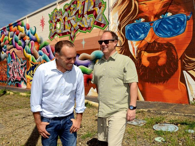 Asheville artists Jon Sarver, left, and Todd Fowler talk about growing more urban artwork onto buildings around West Asheville in front of a large mural on the Sky Lanes Bowling Alley.   William Woody / wwoody@citizen-times.com, William Woody / wwoody@citizen-times.com