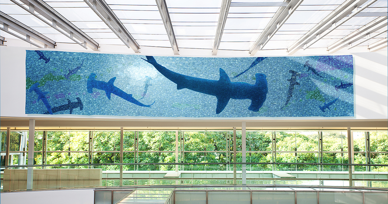 """""""Hammerhead""""  309 L x 59"""" H x 2"""" D, postage stamps on aluminum  CLIENT: Cyber security company  THEIR STORY: Always under attack. Always vigilant.  ART INSPIRATION: I wanted to give the feeling of always being under threat."""