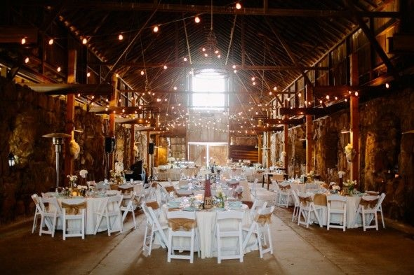 Barn Wedding with hanging lights and white table linens with white chairs