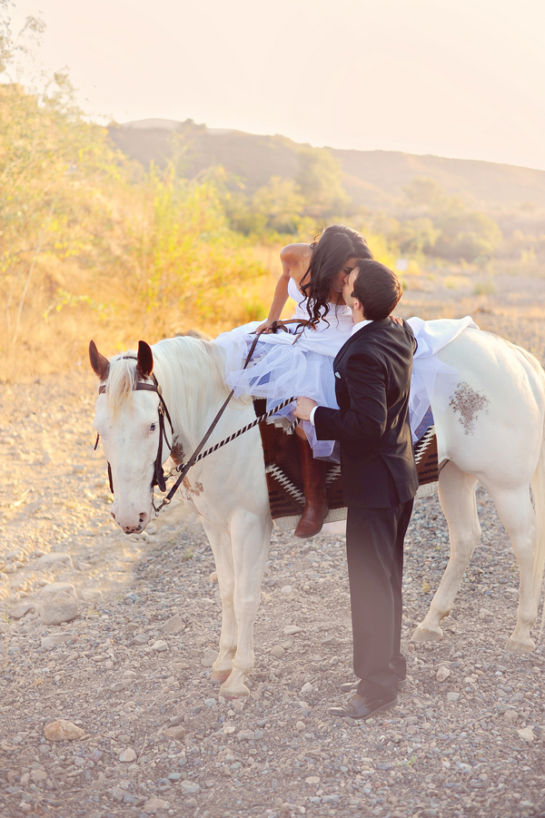 Sweet photo of a bride on a white horse kissing her groom   from Arina B Photography