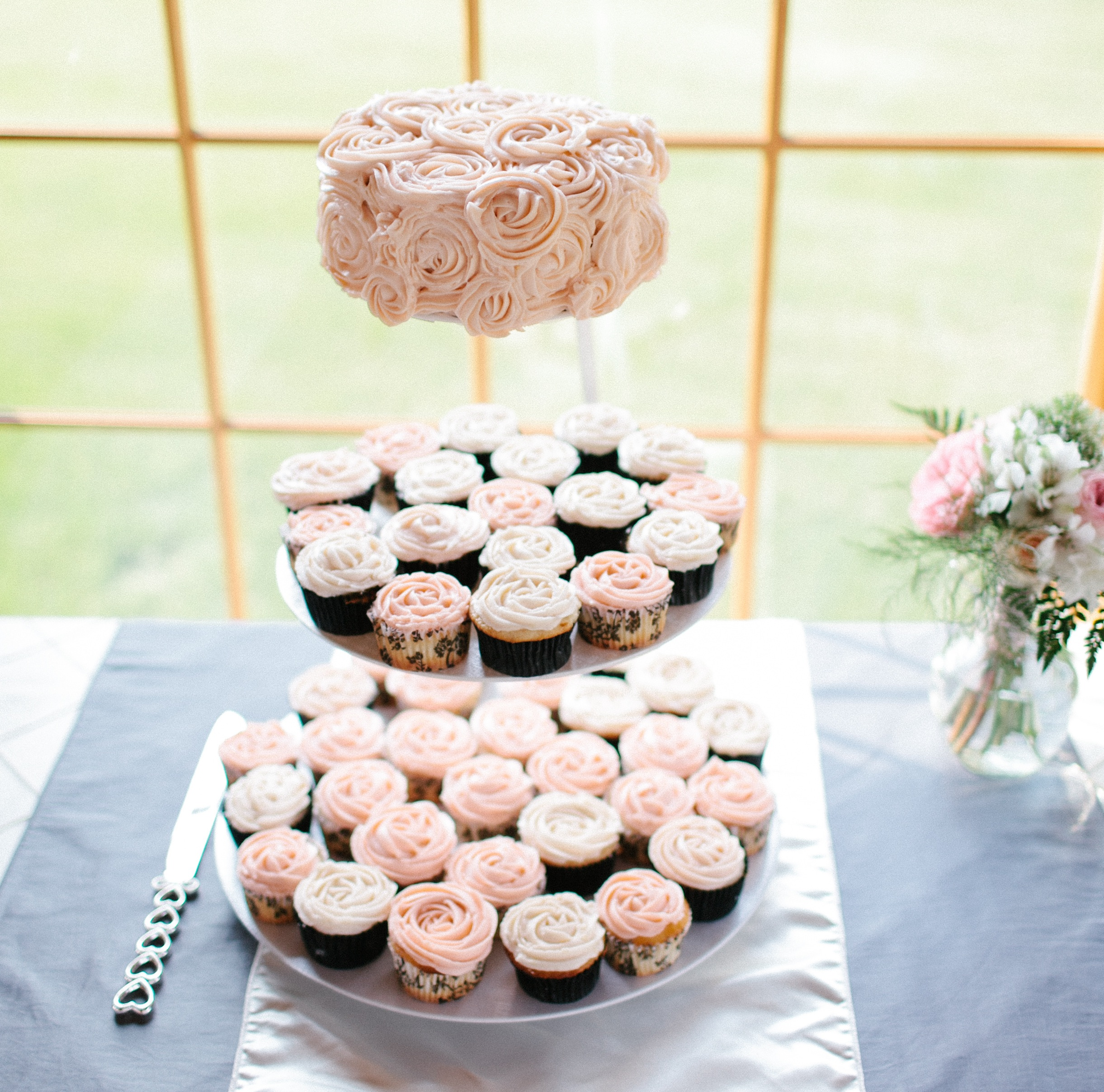 Light Pink Wedding Cupcakes topped with a Rosette Frosted Cake | photo by blf Studios | wedding by Madeline's Weddings