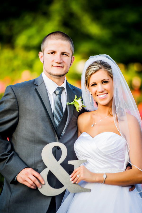 Bride and Groom holding ampersand sign | photo by Ross Costanza Photography | as seen on www.BrendasWeddingBlog.com