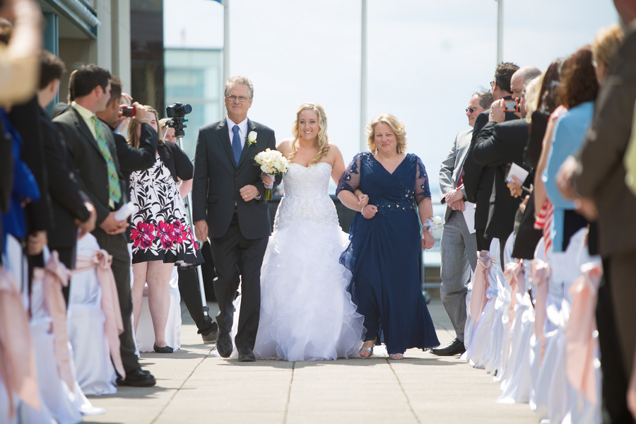 Bride walking down the aisle with her parents, mom in a pretty blue dress | photo by Real Image Photography | as seen on www.brendasweddingblog.com