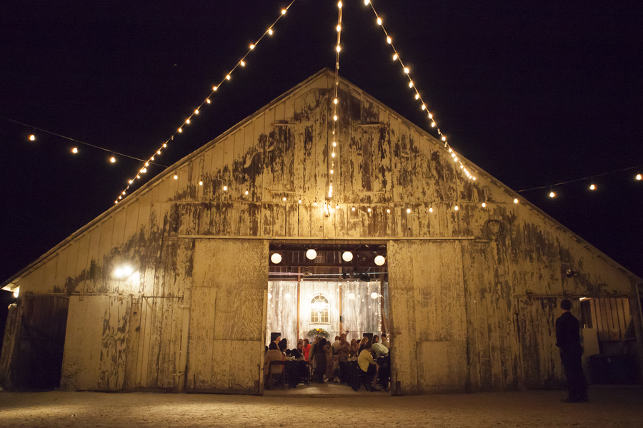 DIY Barn Wedding - illuminated barn with twinkling lights at night / photo by Town Country Studios / as seen on www.BrendasWeddingBlog.com