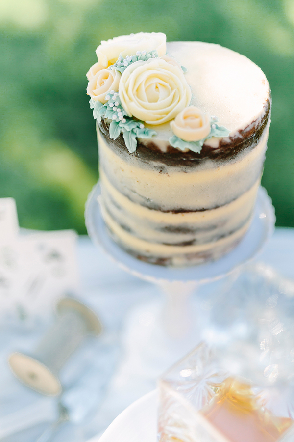 Pretty yellow naked wedding cake with buttercream frosted flowers on top - photo by Destination Wedding Photographer Linda-Pauline Pehrsdotter in Sweden