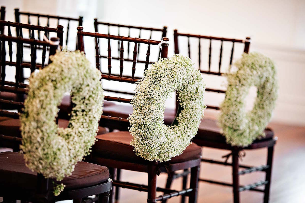 Love these baby's breath wreaths on the wedding ceremony chairs / beautiful wedding ceremony decorations / photo by Rae Leytham Photography / St. Augustine Florida