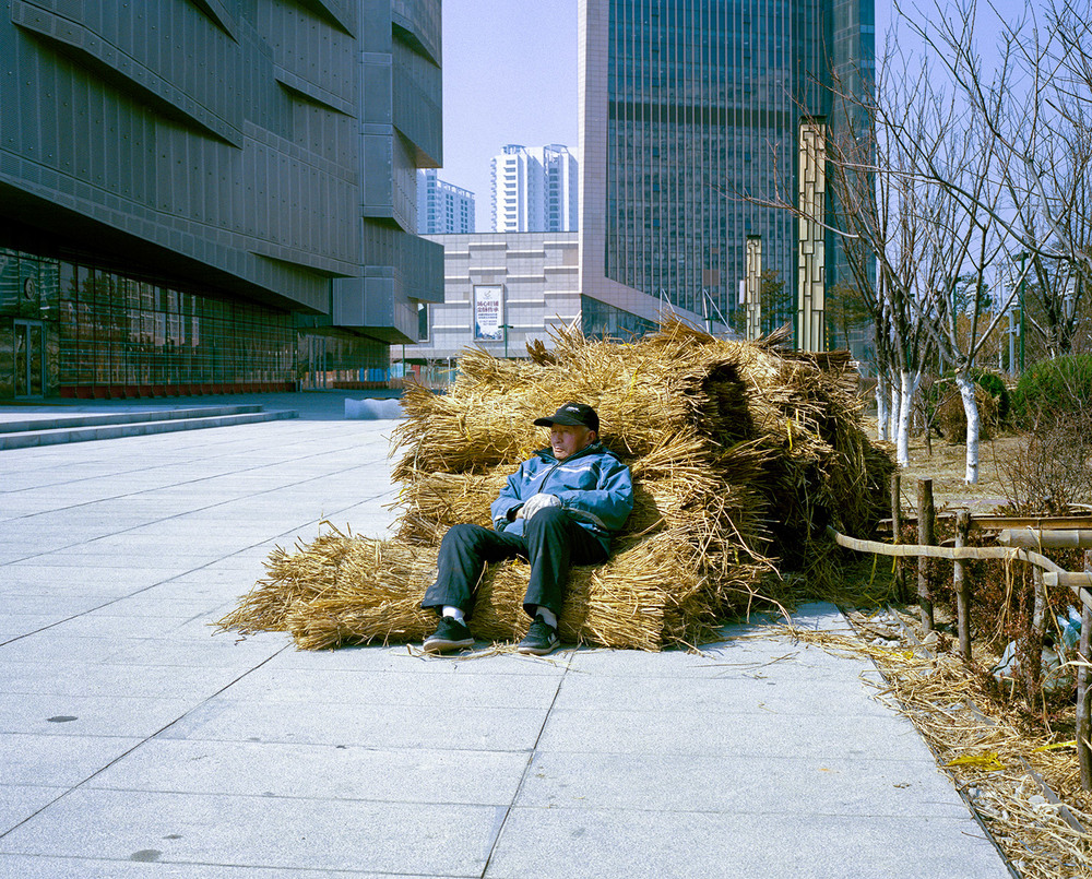 An old man resting on pack of straw in the middle of Yingkou new Harbour district